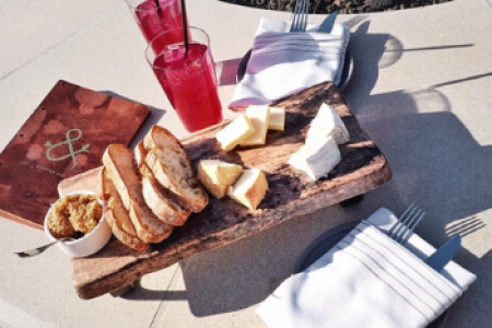 Closeup of a cheeseboard, drinks and silverware