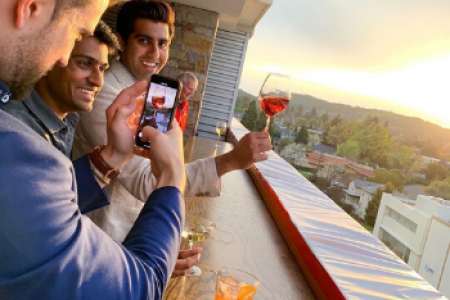 Three men standing on a balcony overlooking downtown Napa, toasting with wine