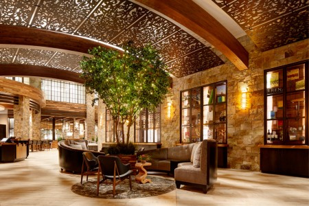Wine-country-inspired lobbywith barrel-like ceiling, lit tree and centered seating