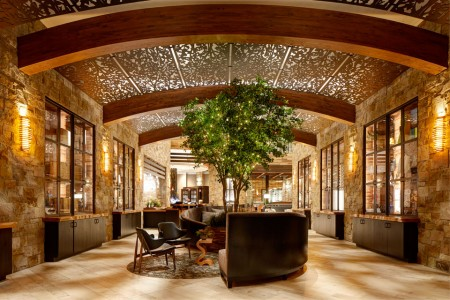 Archer Hotel Napa —Wine-country-inspired lobbywith barrel-like ceiling, lit tree and centered seating