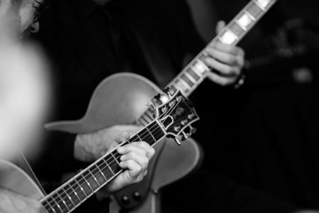 Black-and-white closeup of guitar players