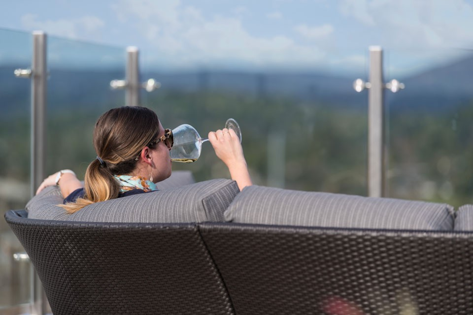 Woman drinking wine  on a rooftop sofa