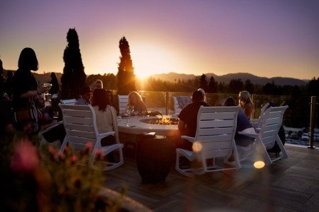 Archer's Rooftop — seating at the fire pit with a sunset skyline view
