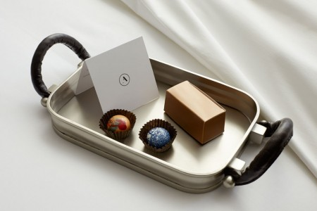 Turndown treat on bed - CIA Chocolates on metal tray with a card
