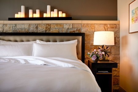 Deluxe King Balcony - a stone wainscot candle-lit wall behind a platform bed and nightstand