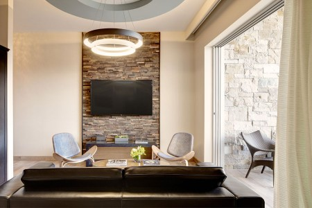 Archer's Den - living area with seating, 65-inch flat-screen TV and entrance to private balcony