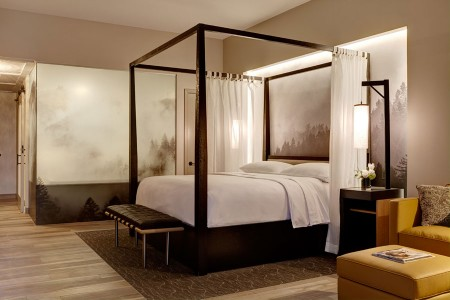 Archer King Balcony Suite - four-poster canopy-draped bed backdropped by Robert Buelteman's ethereal black-and-white Napa vineyard photograph