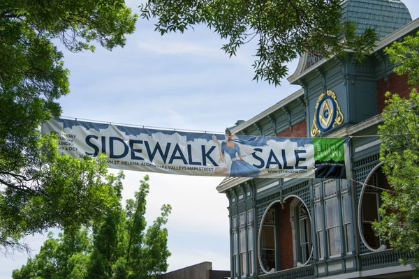 Sidewalk Sale Sign Hung up High attached to an old building and a tree