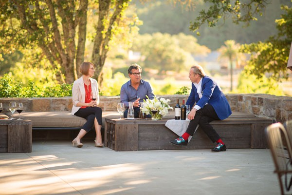 Two Men and A Woman Seating on a Terrace Drinking Wine