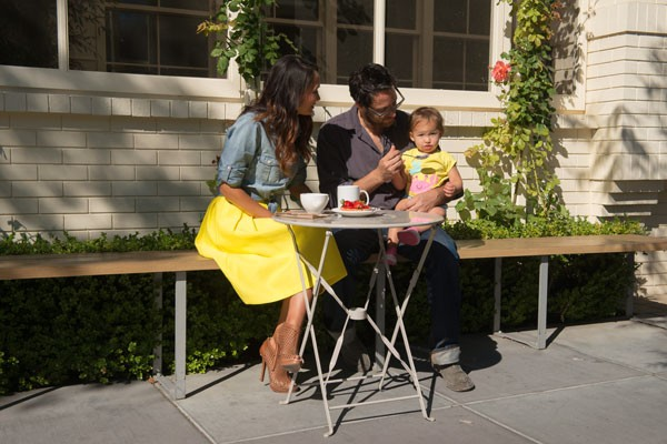 A couple with a young child sitting outside eating breakfast