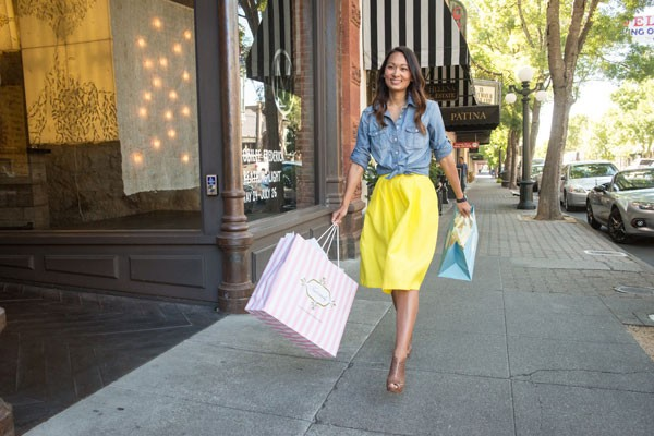 A women cheerfully walking with shopping bags