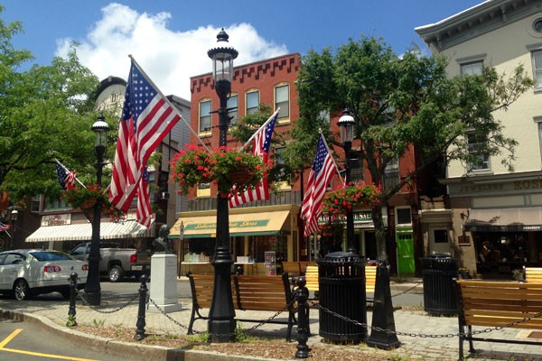 American flags with street shops in the background