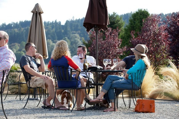 People sitting outside around a patio table with wine and a view