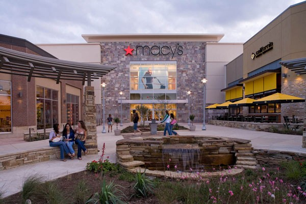 Macy's front entrance with water fountain and people socializing