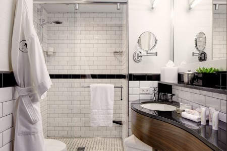 Elegant black-and-white subway-tile bathroom with sink, shower and Frette robe hanging