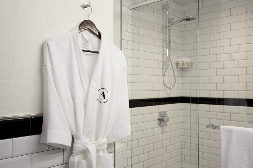 Frette robe hanging in a white subway-tile bathroom
