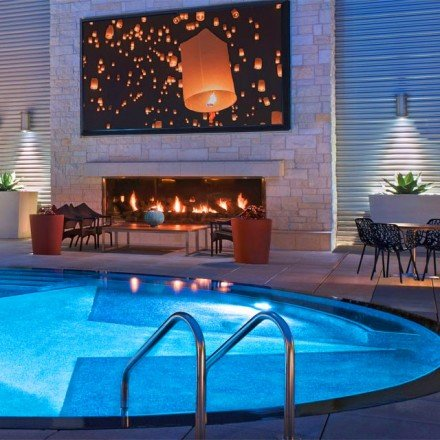 Night view of the outdoor pool lit up, plus the oversized TV and fireplace