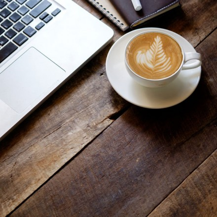Closeup of a laptop computer and cup of coffee on a wood table