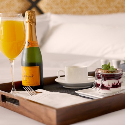 Breakfast tray on bed with food and sparkling wine