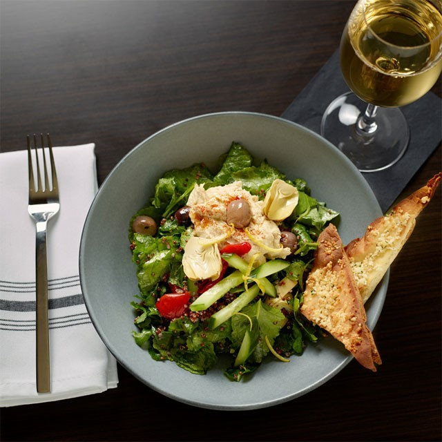 Closeup of salad and glass of wine on table