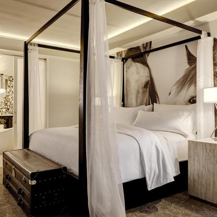 Four-poster bed with a mural of horses