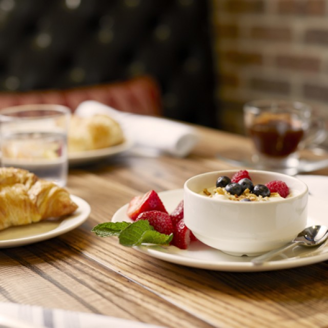 Croissant and granola with berries on a table