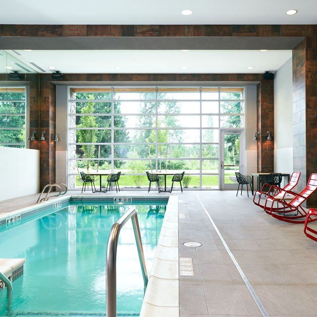 Archer Hotel Burlington — indoor pool with red rocking chairs
