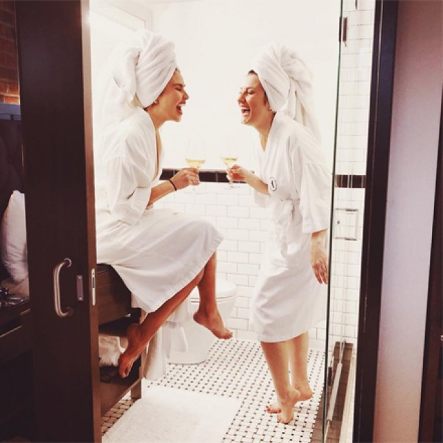 Two women wearing white robes and hair towels, laughing in a bathroom