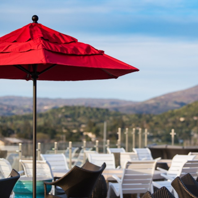 Looking across Sky & Vine Rooftop Bar at the valley in the distance, with a large red umbrella
