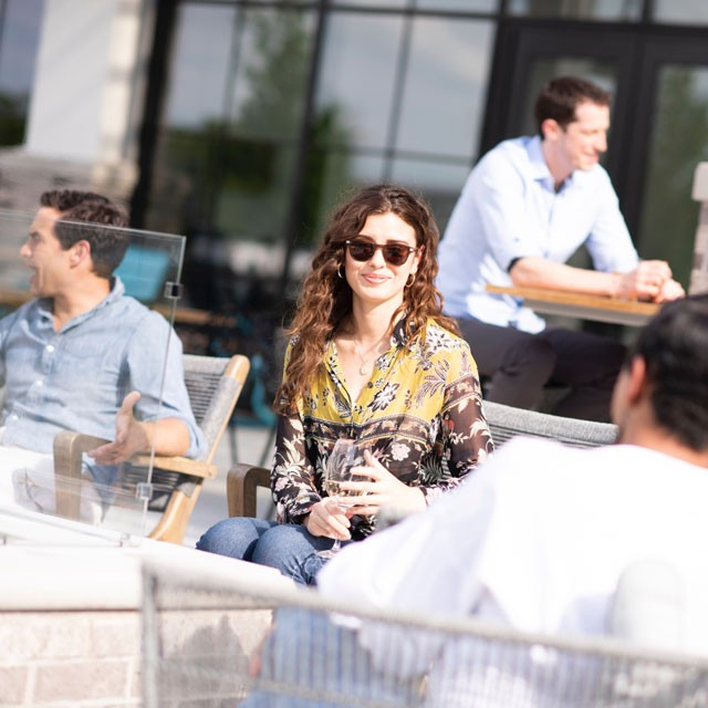 Archer Hotel Burlington - Woman with sunglasses sitting outside on patio