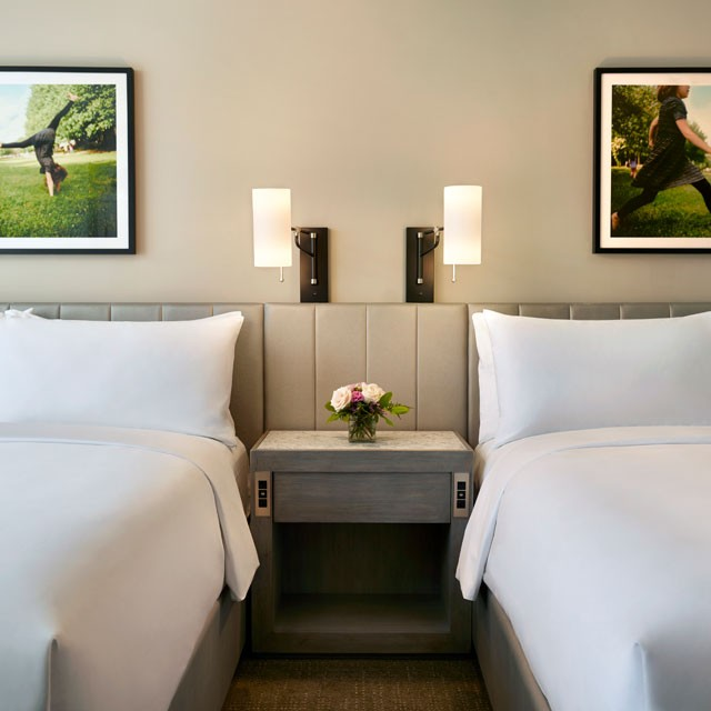 Archer Hotel Redmond - Guest room suite beds with photos above beds of a girl playing in grass