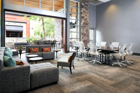 Hospitality Lounge — with floor-to-ceiling natural light from the open glass garage door