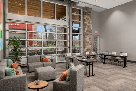 Hospitality Lounge — with floor-to-ceiling natural light from the glass garage door
