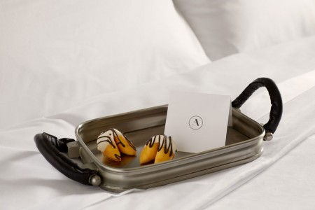 Turndown treat on bed - fortune cookies on a tray with a card