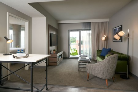 Archer's Den with Balcony - spacious living area with sliding glass door to the private balcony and wall-mounted TV