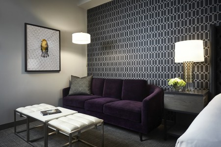 Archer King Suite - living area with mid-century modern eggplant sofa and coffee table
