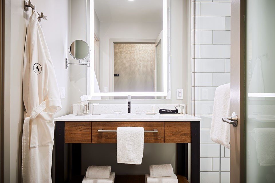 Modern bathroom featuring a weathered iron vanity and white subway-tile walk-in shower